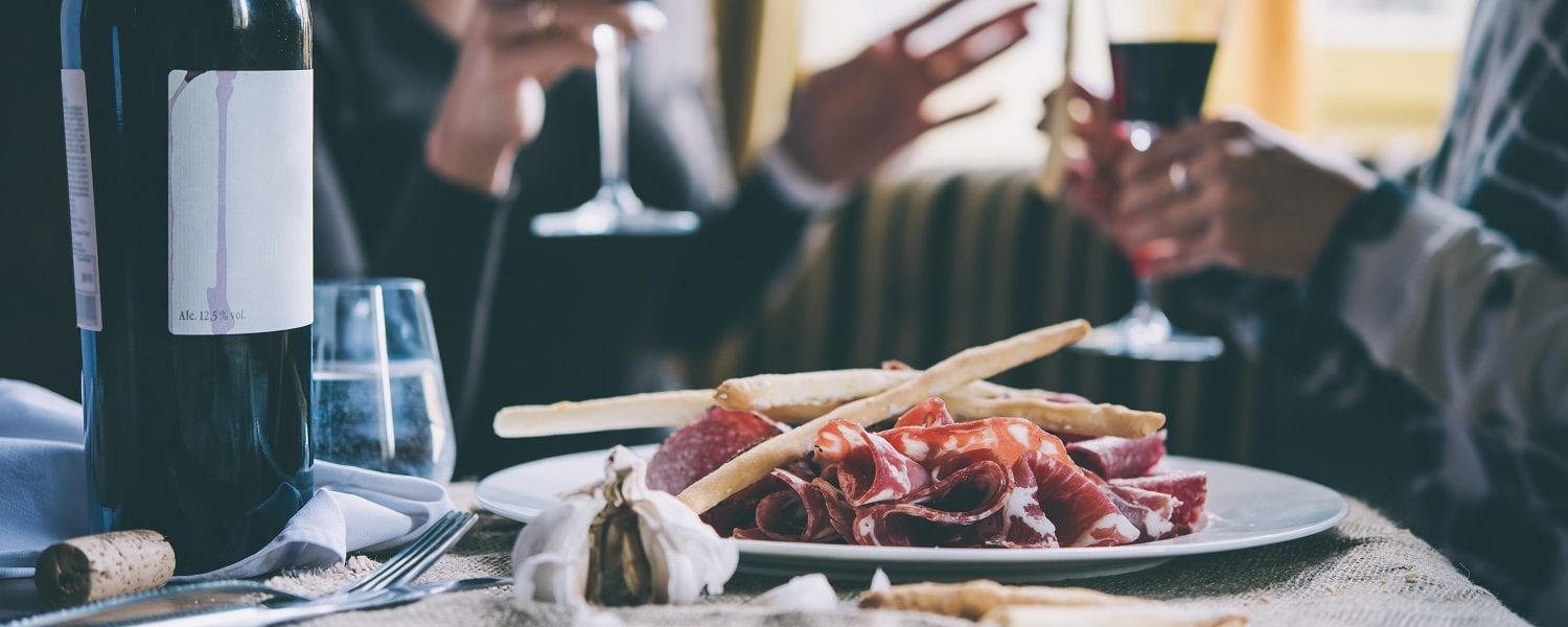 Restaurant table with plate of appetizers and wine. Two people talking on background.