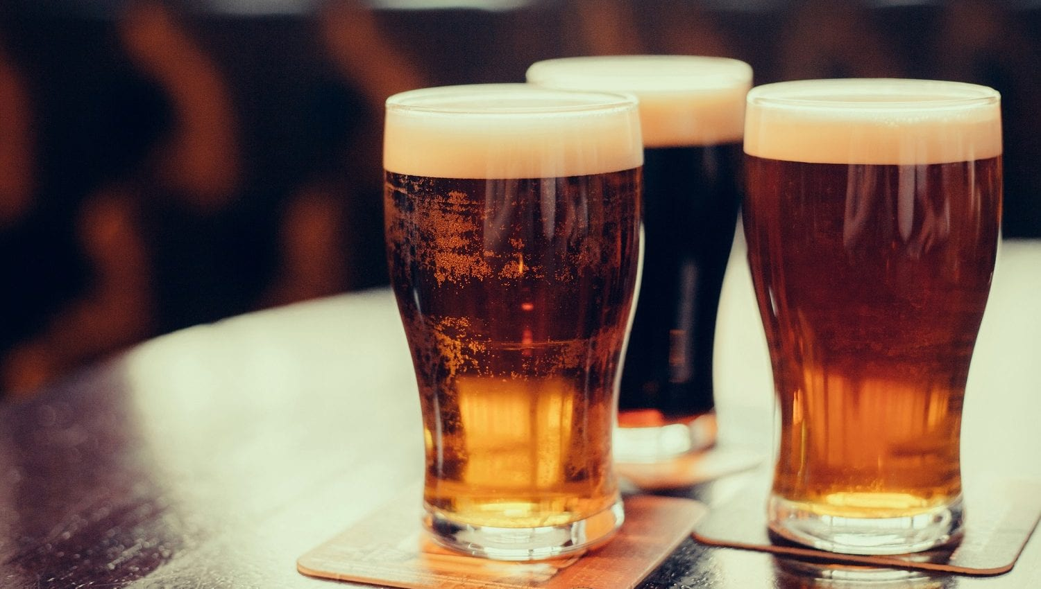 Three glasses of beer in pint glasses