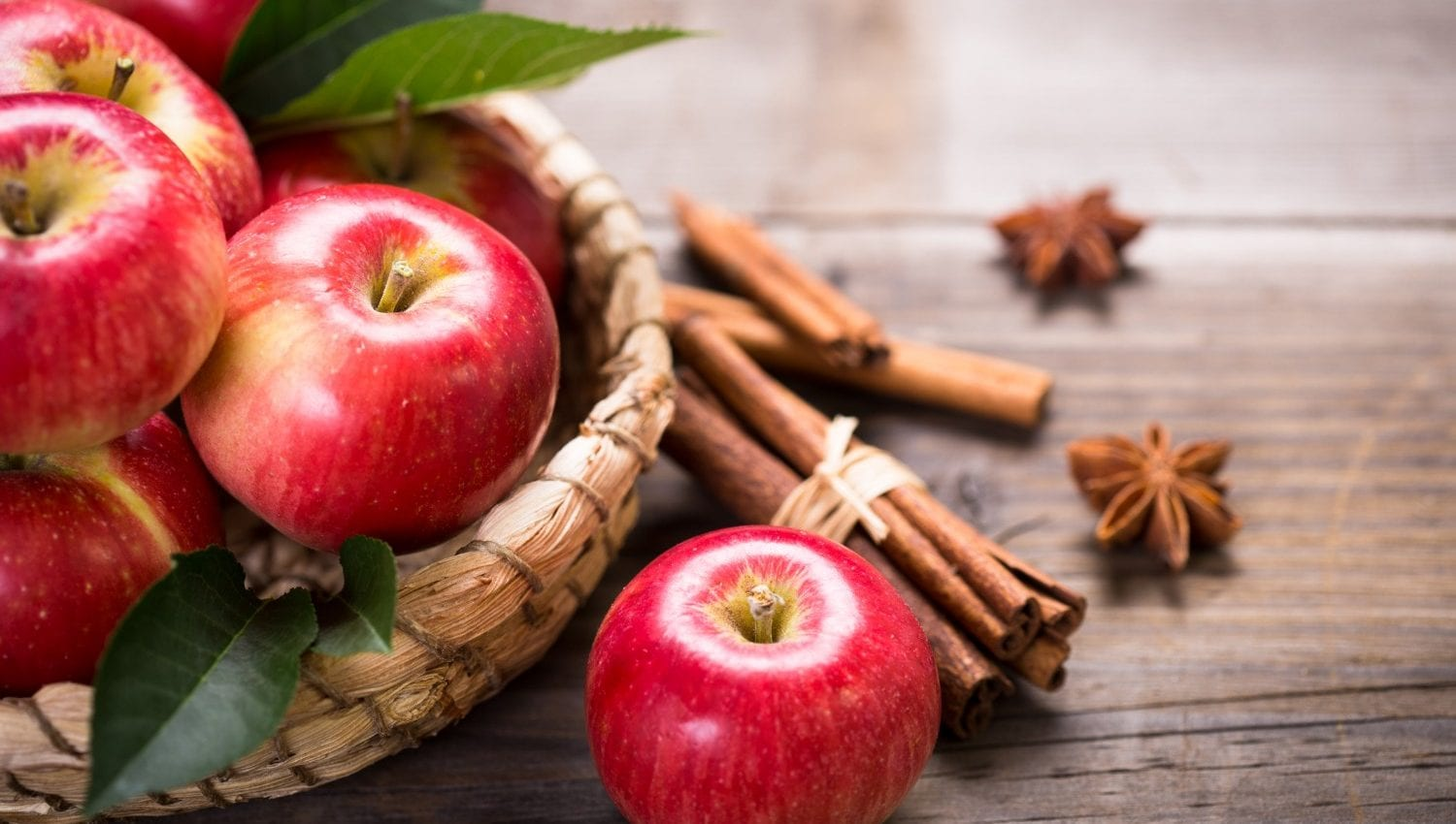 Basket of red apples with cinnamon sticks