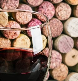 a glass of red wine in front of a background of corks