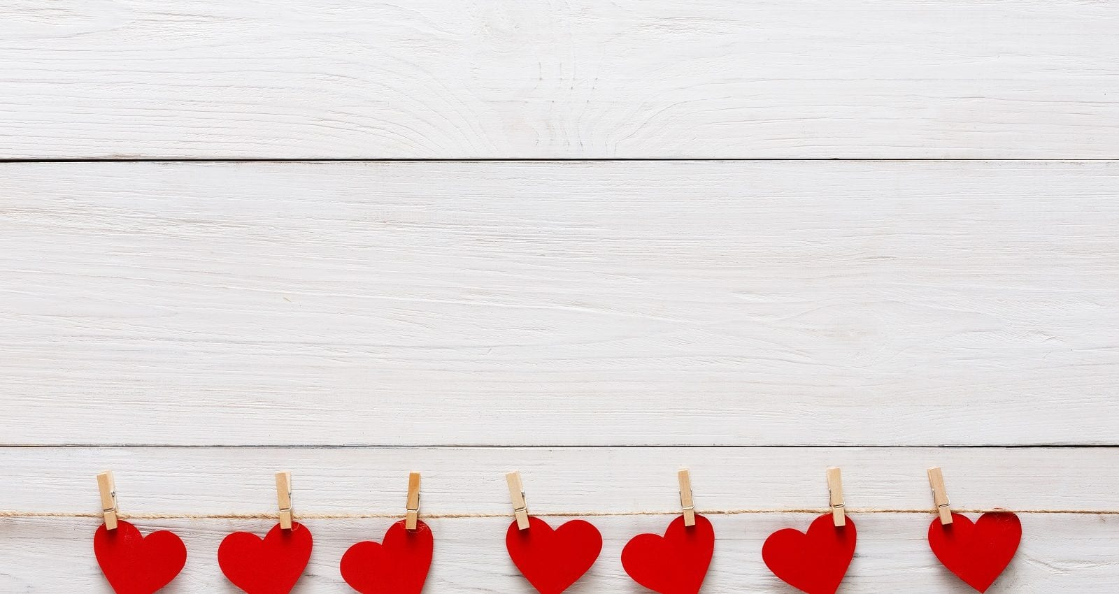 Red paper hearts row border on clothespins on white rustic wood planks