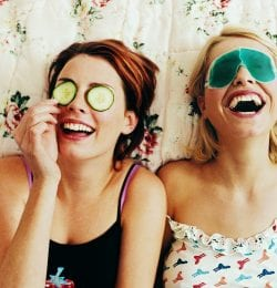 two women laughing together with eye masks on