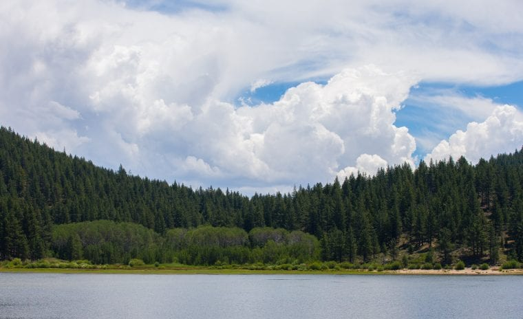 Lake Tahoe Cloudscape – dramatic clouds over Lake Tahoe showing smooth blue water, lush green evergreens, and ample copy space in the upper half of the frame. Lake Tahoe is a very popular U.S. tourist destination, famous for its clear water, natural beauty, year-round recreational opportunities, and proximity to Northern California.