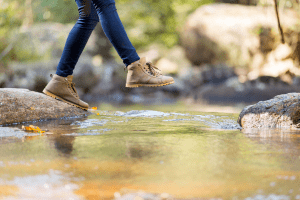person hiking over stream